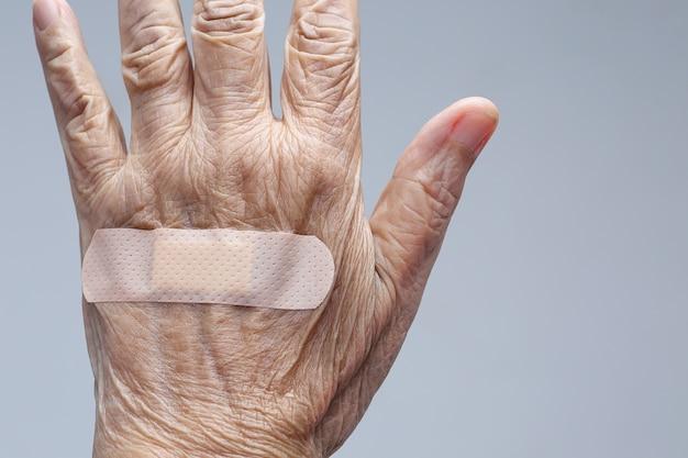 Bejaarde zelfklevend verband op haar hand