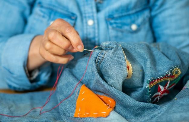Bejaardehanden die op stoffenjeans naaien