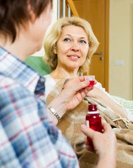 Bejaardentehuiswerknemer die mengsel aan patiënt aanbiedt