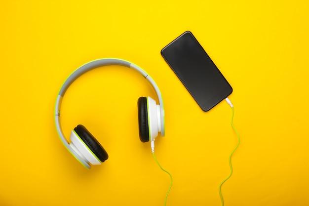 Bekabelde stereohoofdtelefoons met smartphone op geel oppervlak. duizendjarig spul