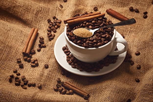 Beker gevuld met koffiebonen en lepel met bruine suiker