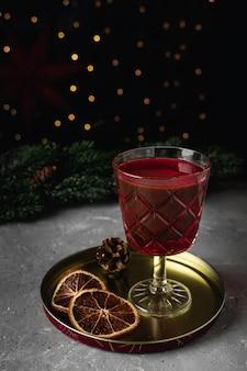 Beker glühwein in transparante mok, gedroogde sinaasappel, kaneelstokje, steranijs