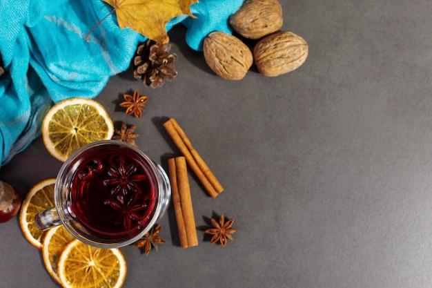 Beker glühwein met kruiden, een sjaal, droge bladeren en sinaasappelen op een stenen tafel. herfststemming, een methode om warm te blijven in de kou, copyspace.