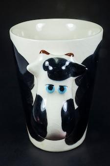 Beker in de vorm van een koe, een zwarte achtergrond, een close-up.