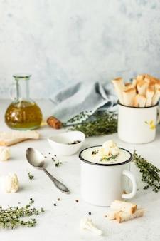 Beker met bloemkoolroomsoep garneer met verse bloemkool, tijm en brood. herfst- of wintercomfortvoedsel. gezond eten.