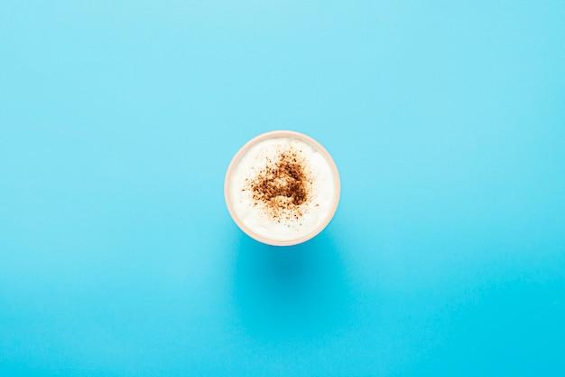 Beker met cappuccino, koffie met schuim op een blauwe ondergrond. concept coffeeshop, barista, ontbijt. . plat lag, bovenaanzicht