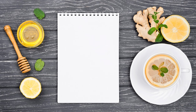 Beker met citroenthee en honing en notebook