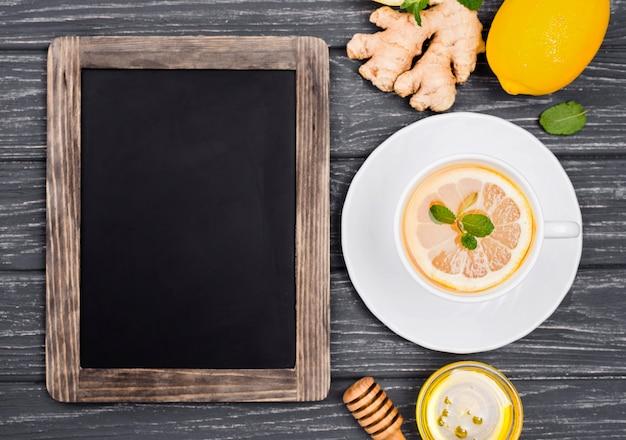 Beker met citroenthee en honing en schoolbord