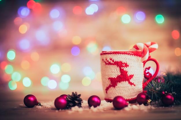 Beker met gebreide kerstherten en kerstballen op feestelijke achtergrond. de foto heeft een lege ruimte voor uw tekst