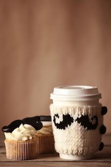 Beker met gebreide omslag en heerlijke cupcakes met snor op onscherpe achtergrond