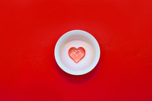 Beker met hartjes op een rode achtergrond. het uitzicht vanaf de top. rode harten gemorst. geïsoleerd op een roze achtergrond. kopieer ruimte