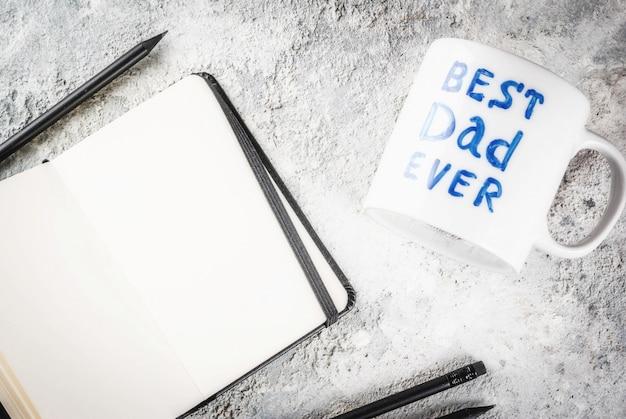 Beker met het opschrift beste vader ooit, zakelijk notitieboek en potloden