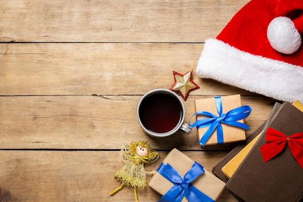 Beker met hete thee, kerstman hoed, cadeau, kerstversiering, boeken op een houten achtergrond. kerstmis, wintervakantie,. plat lag, bovenaanzicht