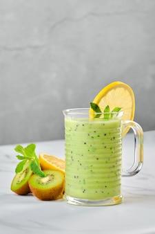 Beker met kiwi en citroen smoothie met munt op marmeren achtergrond