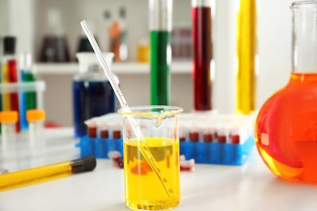 Beker met kleurrijke vloeistoffen op tafel Premium Foto