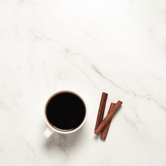 Beker met koffie en kaneelstokjes op een marmeren tafel. plat lag, bovenaanzicht
