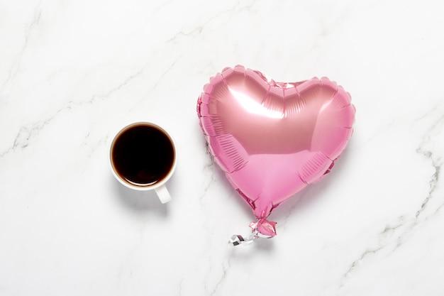 Beker met koffie en luchtballonhart op een marmeren tafel
