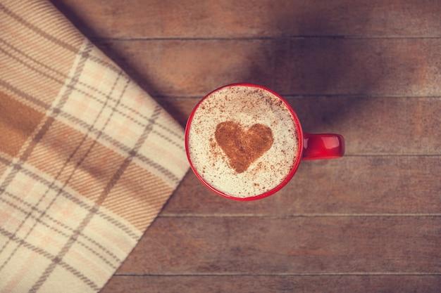 Beker met koffie en vorm van het cacaohart erop en sjaal
