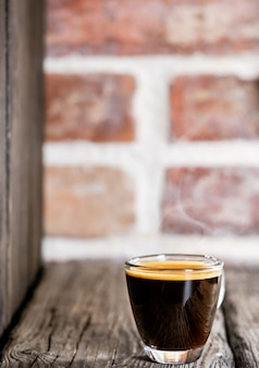 Beker met koffie espresso gerangschikt op een oude bakstenen tafel. close-up, selectieve aandacht, kopieer ruimte, minimalisme