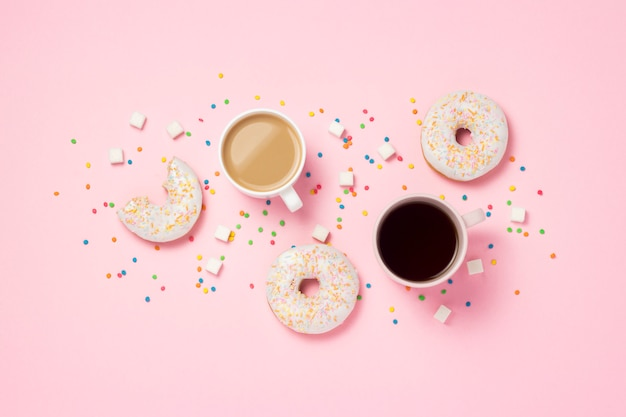 Beker met koffie of thee, verse smakelijke zoete donuts, kleurrijke decoratieve snoepjes, suikerklontjes op een roze achtergrond. bakkerijconcept, vers gebak, heerlijk ontbijt, fast food. plat lag, bovenaanzicht.