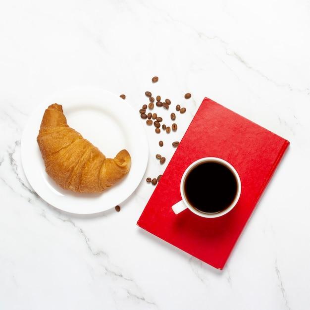 Beker met koffie op een boek, croissant en koffiebonen op een marmeren tafel. het concept van ontbijt, freelance, werk, frans ontbijt. plat lag, bovenaanzicht