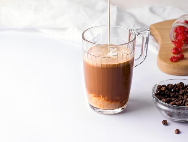 Beker met koffie waarin melk of room op een witte achtergrond wordt gegoten