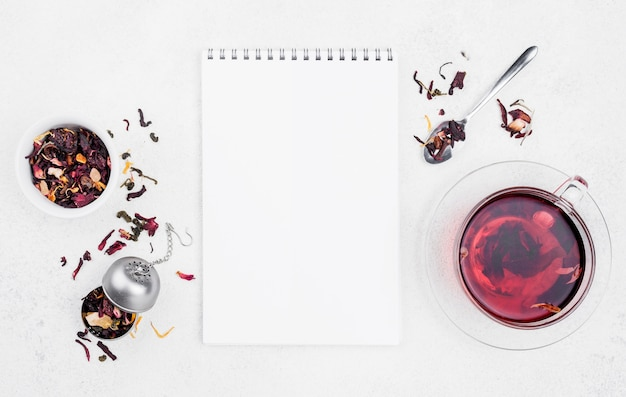 Beker met kruidenthee naast notebook