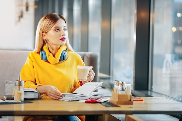 Beker met latte. mooie vrouw met blauwe ogen die een kopje met smakelijke latte vasthoudt terwijl ze in de cafetaria zit