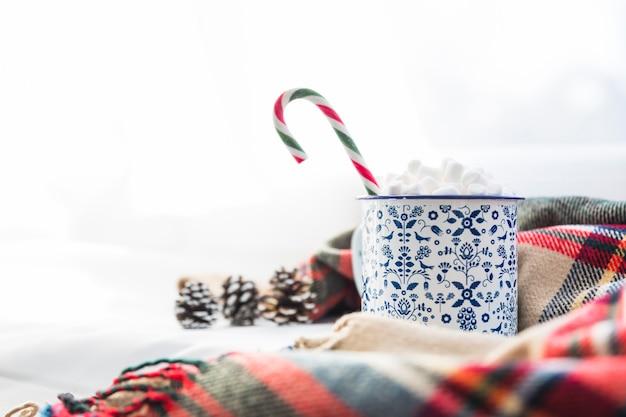 Beker met marshmallow en lolly in de buurt van sjaal en haken en ogen
