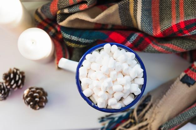 Beker met marshmallow in de buurt van kaarsen en sjaal