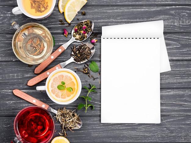Beker met thee en kruiden naast en notebook