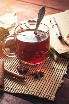 Beker met thee, gedroogde theebladeren op ambachtelijke papier, suiker plakjes envelop en pen op een donkere houten tafel