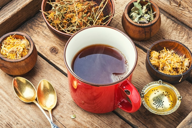 Beker met thee van geneeskrachtige kruiden. diverse kruidenthee-ingrediënten