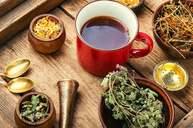 Beker met thee van geneeskrachtige kruiden op een houten ondergrond