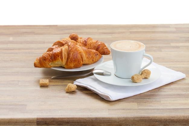 Beker met verse espressokoffie en croissant die op wit wordt geïsoleerd