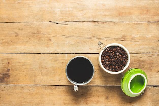 Beker met verse koffie en een blikje met koffiebonen op een houten tafel.