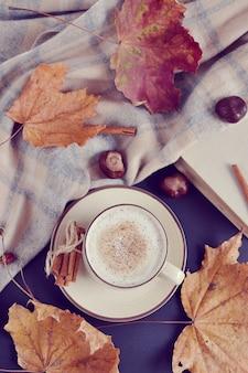 Beker met warme koffie cappuccino herfsttijd gele bladeren kastanjes