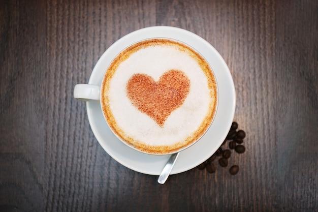 Beker met warme smakelijke koffie op houten tafel, close-up