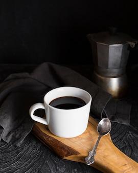 Beker met zwarte koffie op een houten bord