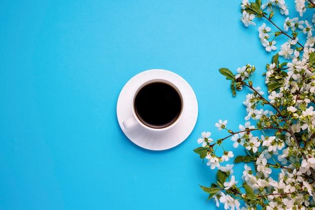 Beker met zwarte koffie, takken van een lente boom met witte bloemen op een blauwe ondergrond. plat lag, bovenaanzicht