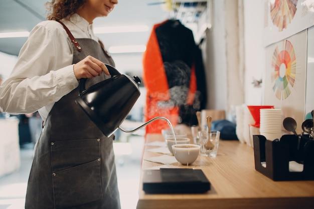 Beker proever meisje met theepot pourover proeverij degustatie koffie kwaliteitstest. koffie cuppen.