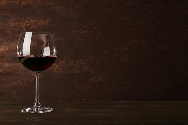 Beker rode wijn op houten tafel op houten muur