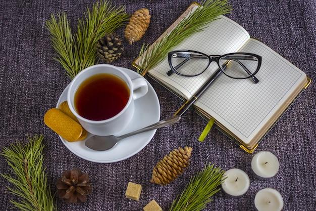 Beker van geurige hete thee tussen kerstboomtakken en dennenappels op een plaid.