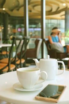 Beker van hete groene thee en witte theepot met een mobiele telefoon op cafe's tafel
