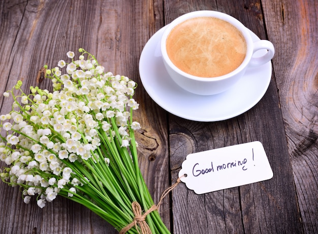 Beker van hete zwarte koffie en een boeket van verse lelietje-van-dalen op een grijze houten oppervlakte