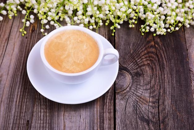 Beker van hete zwarte koffie op een grijze houten oppervlak
