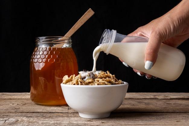 Beker van ontbijtgranen met melk en honing