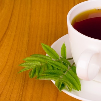 Beker van zwarte thee met kruiden