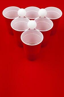 Bekers en plastic bal op rode achtergrond. beer pong spel