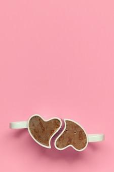 Bekers met koffie op roze achtergrond. bovenaanzicht van valentijnsdag concept met kopie ruimte